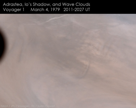 Adrastea, Io's shadow, and wave clouds on Jupiter