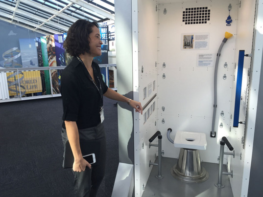 California Science Center's Devin Waller with the Journey to Space exhibit space toilet