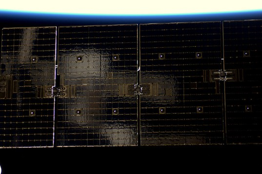 Soyuz reflected in Dragon solar array