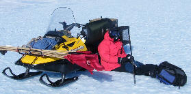 Deon eats lunch hunched behind his ski-doo to keep out of the                   wind.