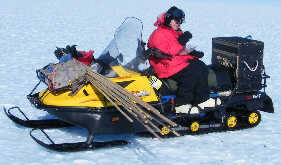 Amy eats lunch sitting proud and tall on her ski-doo; screw the                   wind.