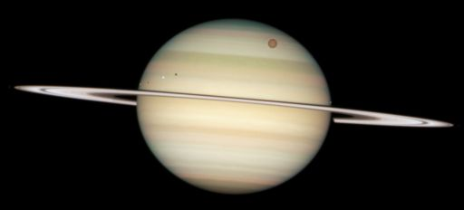 Hubble catches four moons on the face of Saturn