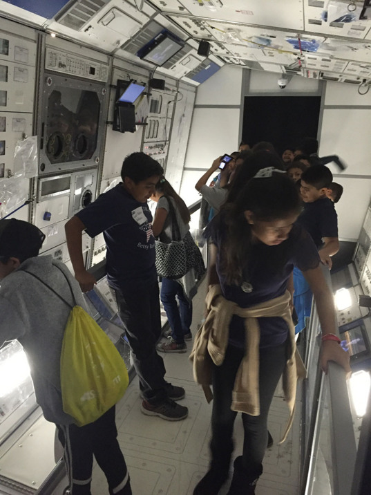 Kids in rotating ISS Destiny module mock-up in the Journey to Space exhibit