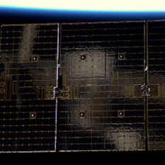 Soyuz reflected in Dragon solar array