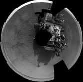 A mosaic of 20 full-resolution images taken from Curiosity's left Navcam on the second day after landing shows the rover, with a dirty deck, sitting on a gravelly plain, surrounded by mountains.
