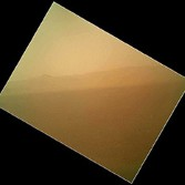 Curiosity's MAHLI (Hand Lens Imager) looks to the north of the rover on the afternoon of sol 1, the first day after landing. In the distance, the image shows the rim of Gale Crater. The image is murky because the MAHLI's removable dust cover is apparently coated with dust blown onto the camera during the rover's terminal descent.