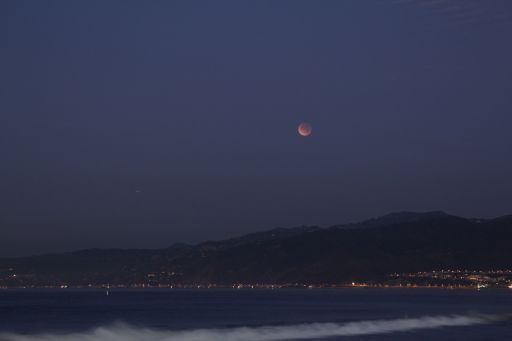 Eclipsed Moon setting over Santa Monica beach
